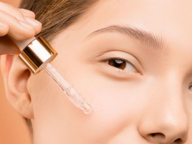 woman applying facial serum